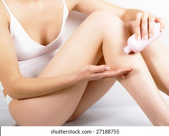 The girl in white pants and a vest rubs a cream to itself in a skin