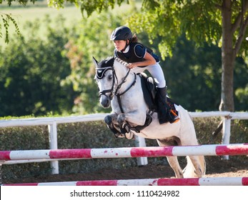 Girl with white pony jumping over the hurdle on equine competition