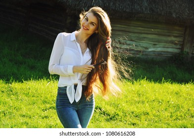 A girl in a white shirt and jeans combs her hair. Young woman with long thick hair