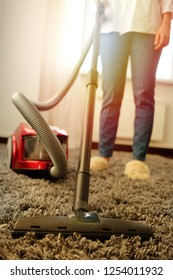 Girl in a white shirt and jeans doing cleaning with a vacuum cleaner