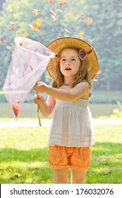 A girl in a white shirt and orange shorts catches leaves in a net.