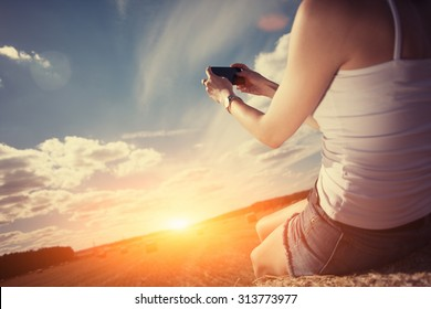 Girl in white shirt sitting on haystack taking photo with mobile phone at sunset (intentional sun glare)