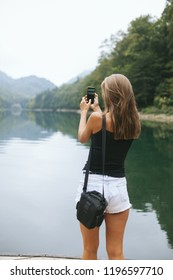 girl in white shorts takes pictures on the smartphone lake