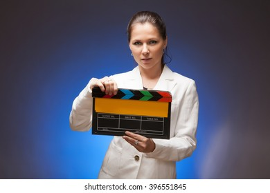 The girl in a white suit with a movie clapper.