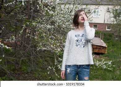 A girl in a white sweater dreamily closes her eyes from the bright sun in the garden near the blooming cherry.