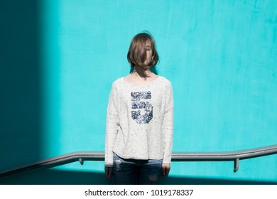 A girl in a white sweater dreamily closes her eyes from the bright sun opposite the blue wall in the underpass