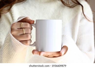 Girl in white sweater holding white coffee mug  , white porcelain mug mock up