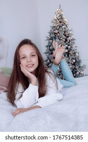 A girl in a white sweater lies on a bed in a bright studio. In the background is a Christmas tree.
