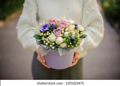 Girl in the white sweather holding in her hands a box of tender white, blue and violet flowers