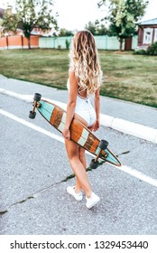 A girl in a white swimsuit bodysuit, walks through summer city on the street, in her hand a board, longboard. Walk fashionable girl with long hair and tanned skin. Back view.