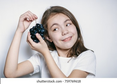 a girl in a white t-shirt and black grapes