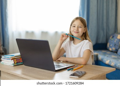 a girl in a white t-shirt, with blond hair, sitting at a table in distance learning, in front of a laptop, on the table textbooks and notebooks, the girl smiles