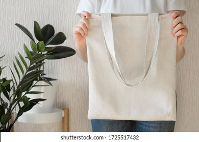 A girl in a white T-shirt and blue jeans holds a reusable eco bag in her hands. Use an eco bag to shop. Zero waste and eco friendly concept. Mockup for design