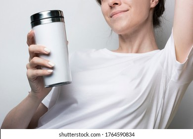 Girl in a white T-shirt holds a thermocup with coffee. Blank for branding. Monochrome mockup