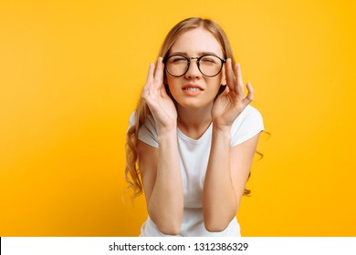 A girl in a white T-shirt, with poor eyesight wears glasses, looking squinting, trying to figure out what is written on a yellow background