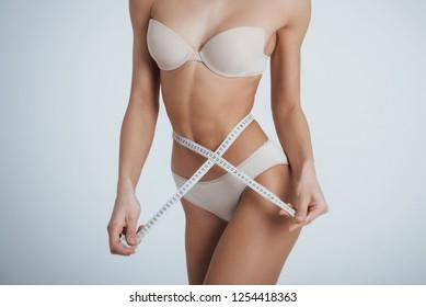 Girl in the white underwear with centimeter tape around her waistline.