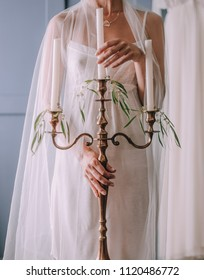 girl in a white veil and underwear holds a candelabra with candles in her hands
