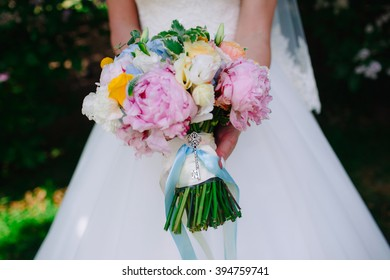 Girl in white wedding dress with a bouquet of pink and white flowers in her hands, standing in the forest