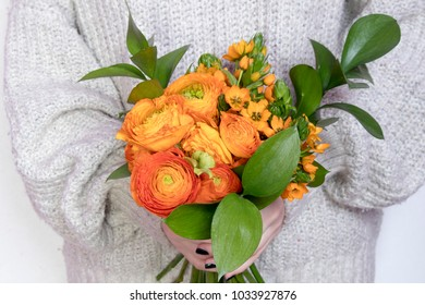 the girl in white wool sweater holds a wedding bouquet of buttercups and Ruscus on the white background