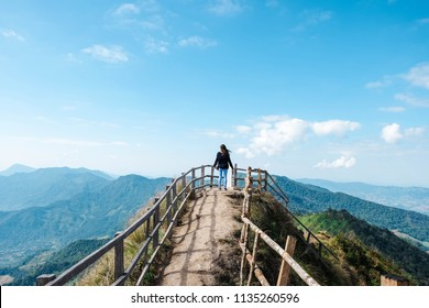 A girl who stand on the peak of Phu Chi Dao mountain at Chiang Rai province, Thailand, with nature trail view point