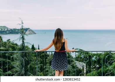 A girl who is standing and looking at the sea photographed from behind.