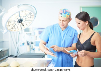 The girl, who wants to correct sagging breasts, at the reception at the plastic surgeon. She tries on the desired breast using a silicone mold
