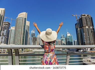 Girl in a wide-brimmed hat standing on the bridge and looks at the Dubai Marina