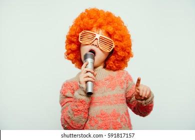 Mädchen in Perücke und Sonnenbrille singen in ein Mikrofon. ein kleines Mädchen, das in einer Perücke mit einem Mikrofon trägt.