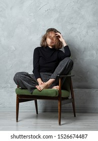 Girl with wild messy hair sitting on armchair with legs