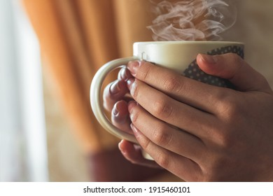 Girl at the window holding a cup of hot coffee