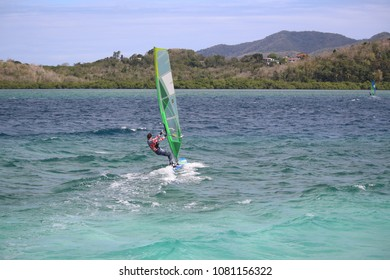 Girl windsurfing in the turquoise Caribbean water near Trois Ilets, Martinique