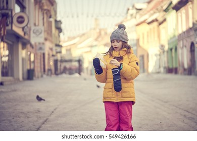 Girl in winter clothes eats her boiled corn