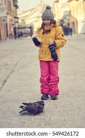Girl in winter clothes feeding pigeons with her boiled corn