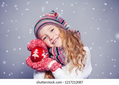 Girl in winter clothes. Happy child. Studio shot