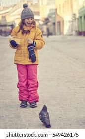 Girl in winter clothes smiles captivated while feeding pigeons with her boiled corn