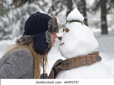 Girl in winter clothing kissing snowman
