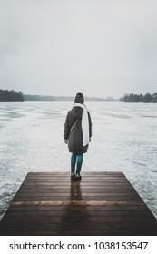 Girl in a winter clothing standing on a wooden bridge overlooking frozen lake and forest. Trakai, Lithuania, Europe.