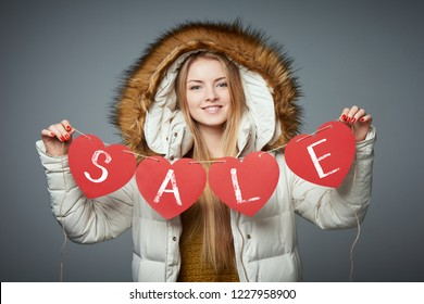 Girl in winter coat with hood on holding four hearts garland with text sale smiling looking at camera on grey studio background