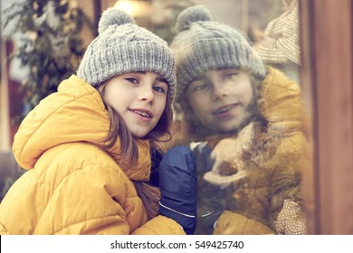 Girl with winter hat and blonde hair reflected on a window