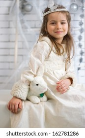 Girl in winter holiday dress with a toy rabbit