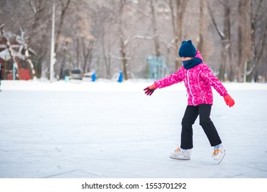 Girl in the winter at the rink. A girl in a pink jacket is skating. Background for text.
