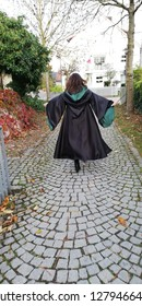 A girl in a witch costume and high heeled boots walking away down the ancient street