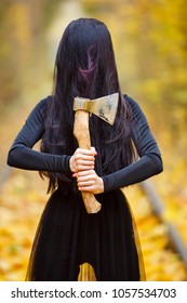 a girl in a witch costume in a long black dress with long black hair covering her face holds an ax in her hands. Day, autumn, a tunnel of yellow autumn leaves.thematic photossesion