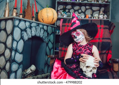 Girl in a witch costume sitting in a chair with a skull in his hands in in halloween decorations