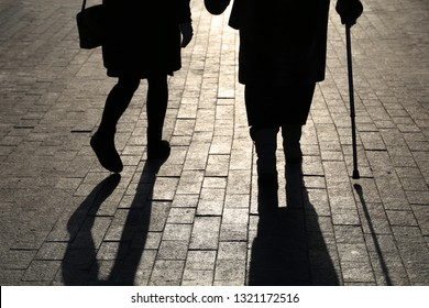 Girl and woman with a cane, black silhouettes and shadows of two people walking on the street. Concept of limping, old age, elderly or blind person
