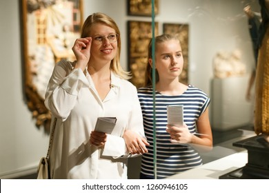 Girl with woman looking with interest at art objects in museum, using guidebook