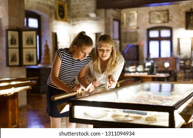 Girl with woman looking with interest at art objects under glass in museum, using guidebook