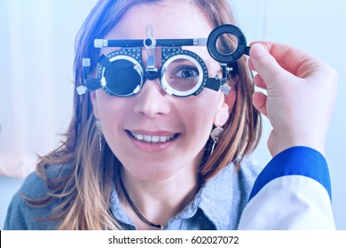 Girl woman in messbrille glasses in ophthalmology clinic. Ophthalmic glasses for diopter detection.