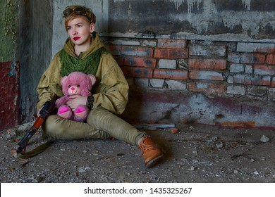 A girl or a woman in military clothes is sitting on the floor and holding a machine gun in one hand and a teddy bear in the other. Emotional scene, perhaps a post-apocalyptic future or a world in war.