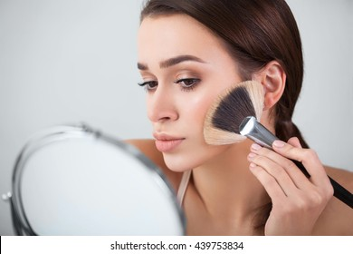 girl, woman in the mirror puts makeup brush